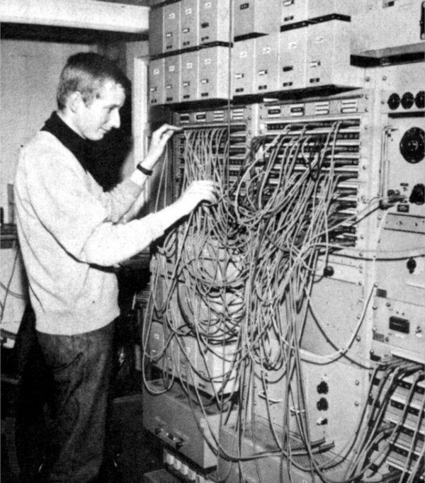 Fotografija iz lipnja 1965. John Baker provjerava spojeve u sobi broj 12 i pokušava se snaći u spletu brojnih kablova koji su bili potrebni za spajanje svih uređaja. Mali uređaji pri vrhu fotografije su BBC-ova Type B pojačala. (Foto: BBC)