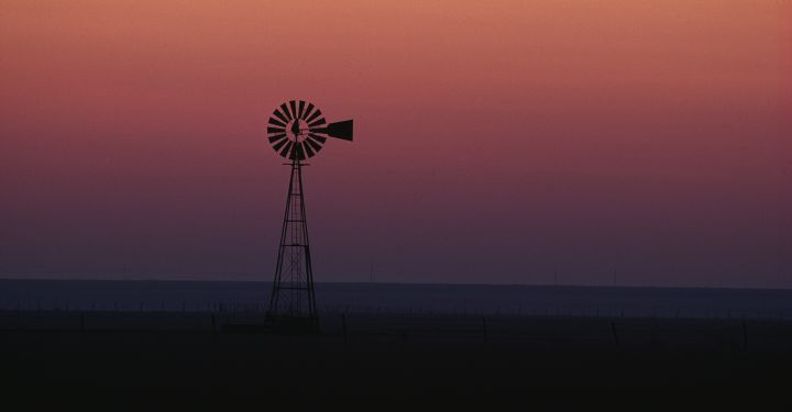 Solitary sentinel of the rural landscape, a wind- mill breaks the flat horizon of a Texas panhandle dawn. The color of the sky runs the spectrum from yellow to violet. The wind blows almost continu- ously across the plains, turning win dmill vanes to pump water for the region's farms and ranches.